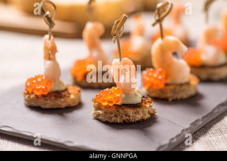 Shrimp Appetizer served on toasted bread with golden Caviar - Stock Photo