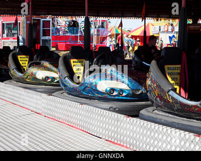 Brightly coloured bumper cars or dodgems awaiting customers on a traveling fairground at the Great Dorset Steam - Stock Photo