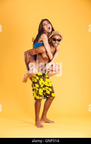 Loving smiling couple in swimwear having fun isolated on the orange background - Stock Photo