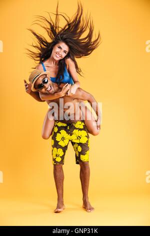 Young happy couple enjoying piggyback ride isolated on orange background - Stock Photo