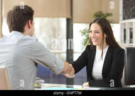Happy businesswoman handshaking with client closing deal in an office interior with a window in the background - Stock Photo