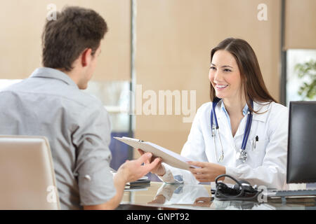 Happy doctor female wearing coat attending to her patient in a consultation while is holding a medical history - Stock Photo