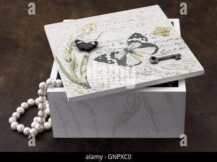 White jewellery box isolated on brown background - Stock Photo