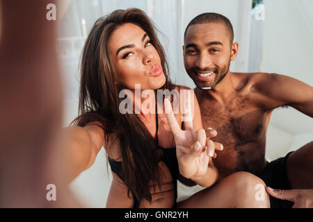 Young smiling couple in love making selfie while sitting at the beach bed and showing v sign - Stock Photo