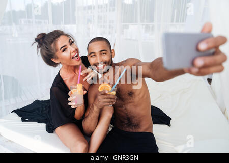 Happy smiling multiracial couple making selfie and holding cocktails at the beach - Stock Photo