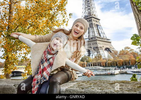 Autumn getaways in Paris with family. Portrait of smiling mother and daughter travellers on embankment in Paris, - Stock Photo