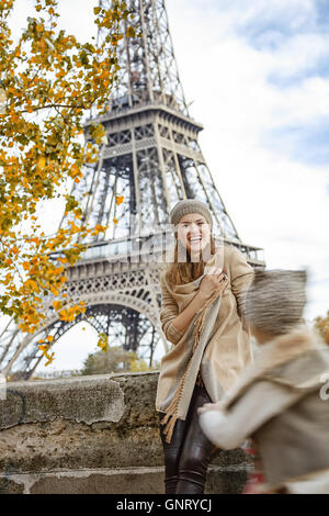 Autumn getaways in Paris with family. happy mother and daughter tourists on embankment in Paris, France playing - Stock Photo