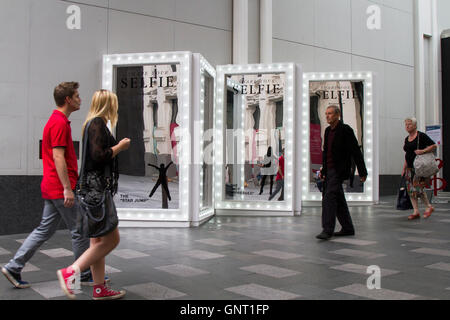 Share your Selfie. Mirror optical Illusion, an Invitation to, people passing, to take a selfie, mirror, woman, photo, - Stock Photo