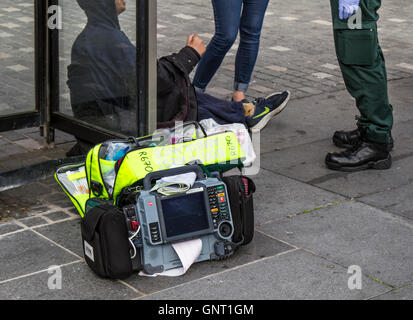 First responder giving medical treatment to seated person in Williamson Square, Liverpool, Merseyside, UK - Stock Photo