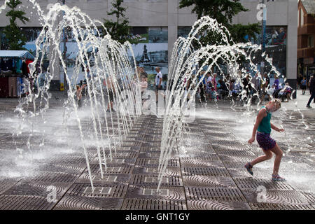 Hot summer day when children played for hours in the pulsating water jet fountains of Williamson Square, while parents - Stock Photo