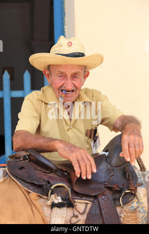 Old gentleman with Cuban cigar leaning on his donkey in Trinidad, Cuba - Stock Photo