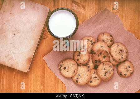 Homemade chocolate chip cookies, milk cup and vintage book on rustic wooden table, top view - Stock Photo