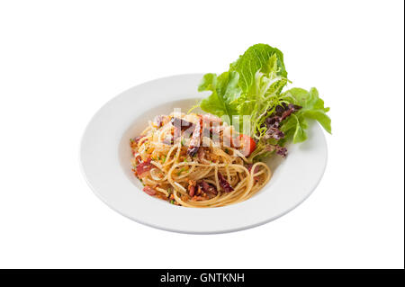Front view of Thai, Japanese, and European fusion food style spicy pasta with bacon and dried chili in ceramic dish - Stock Photo