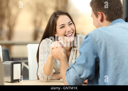 Happy couple dating and flirting and holding hands together in a coffee shop with a sunset light outdoor in the - Stock Photo