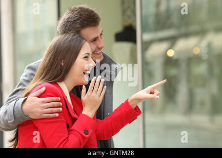 Excited fashion couple shopping and watching in a storefront in a town street - Stock Photo