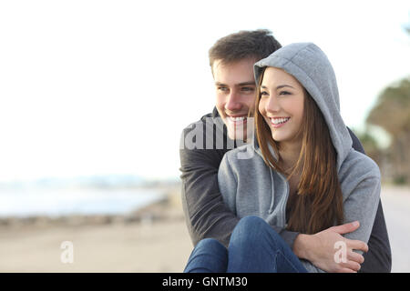 Casual happy teenager couple dating and hugging sitting outdoor and looking at horizon in the beach - Stock Photo