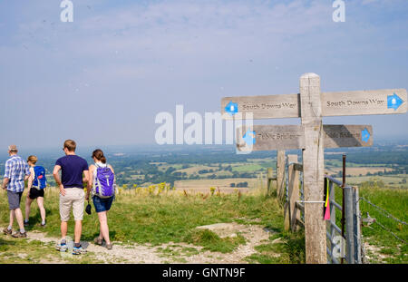 Country footpath signpost and people walking on South Downs Way trail in South Downs National Park countryside. - Stock Photo