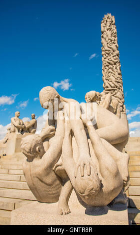 Granite Monolith and Children playing at the base of the statue, Vigeland Park, Oslo, Norway - Stock Photo