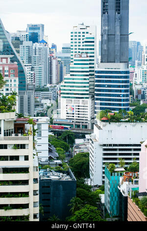View of the Skytrain passing between skyscrapers in Bangkok - Stock Photo