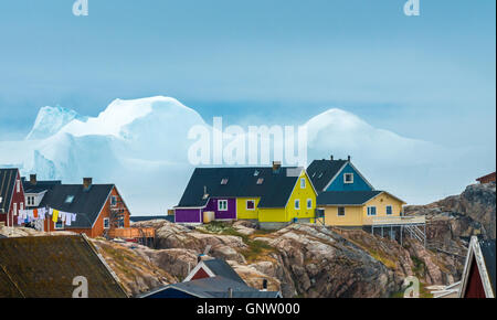 Houses in Ilulissat with huge stranded icebergs at the mouth of the icefjord in the background, West Greenland - Stock Photo