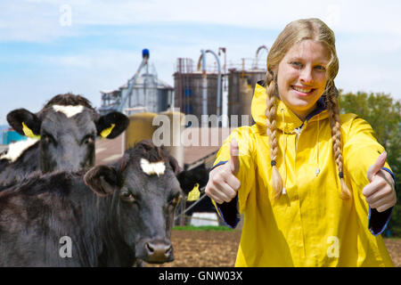 Young farm woman with thumbs up, in background a cattle herd and a farm - Stock Photo