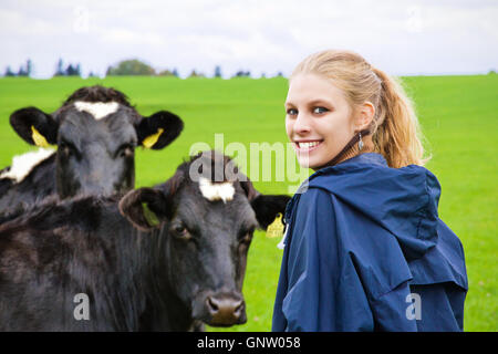 Young farm woman on the paddock, in background a cattle herd - Stock Photo