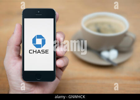 A man looks at his iPhone which displays the Chase bank logo, while sat with a cup of coffee (Editorial use only). - Stock Photo