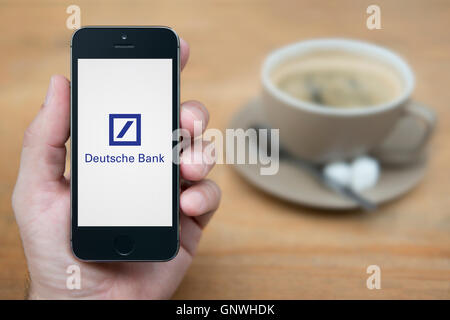 A man looks at his iPhone which displays the Deutsche Bank logo, while sat with a cup of coffee (Editorial use only). - Stock Photo