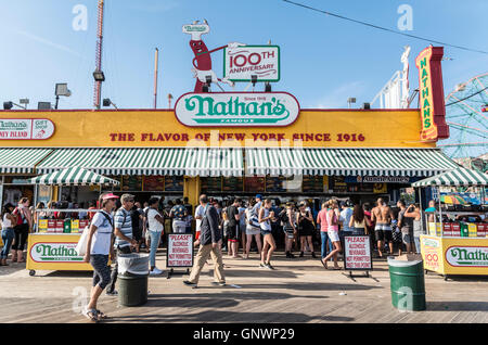 Exterior view of iconic Nathan's Famous hotdog joint on Coney Island boardwalk in Summer, New York. - Stock Photo