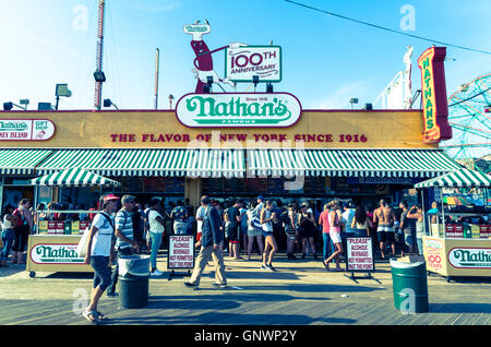 Exterior view of iconic Nathan's Famous hotdog joint on Coney Island boardwalk in Summer, New York in vintage effect - Stock Photo