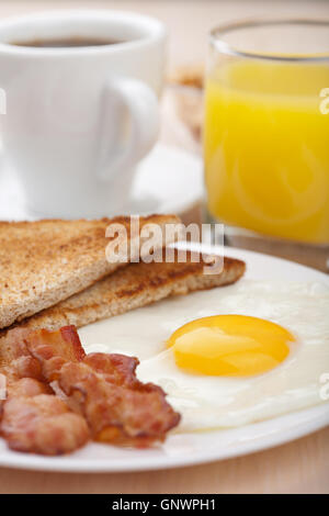 traditional breakfast gnwph1 Orange Coffee Table Heart Shaped Fried Eggs Bread And Orange Juice Stock Photo Image