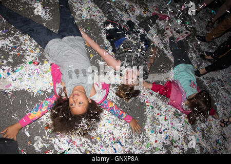 Devizes Wiltshire, UK. 31st Aug, 2016. Children lie on the ground making shapes during the annual confetti battle - Stock Photo