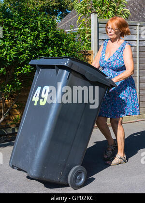 Middle aged lady taking out a rubbish bin. - Stock Photo
