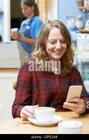 Woman In Coffee Shop Reading Text Message On Mobile Phone - Stock Photo