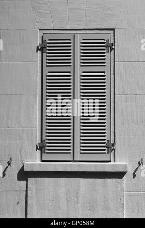 Window with closed shutters in direct sunlight. - Stock Photo