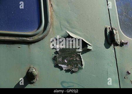 peeling paint patch on a section of the door of an old railway carriage - Stock Photo