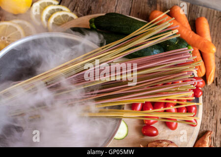 Italian colorful spaghetti and fresh vegetables as typical ingredients of the healthy Italian cuisine - Stock Photo