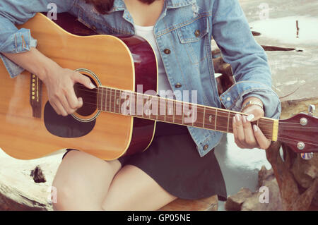 Asian woman playing guitar on wood table. - Stock Photo