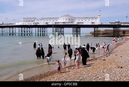 Mix of cultures on Brighton beach with Muslim women and families amongst the crowds enjoying a paddle in the sea - Stock Photo