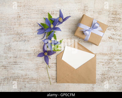 Gift box wrapped in brown kraft paper with violet satin bow, blue flowers and envelope with greeting card on the - Stock Photo