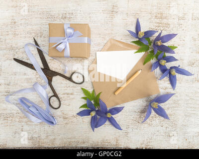 Gift box, blue flowers, scissors, pencil, satin ribbon and envelope with greeting card on the wooden painted board - Stock Photo