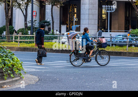 Mother with child cycling in city of Osaka Japan along cycle paths which are generally kept separate from road traffic - Stock Photo