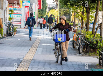 cycling in city of Osaka Japan along cycle paths which are generally kept separate from road traffic - Stock Photo