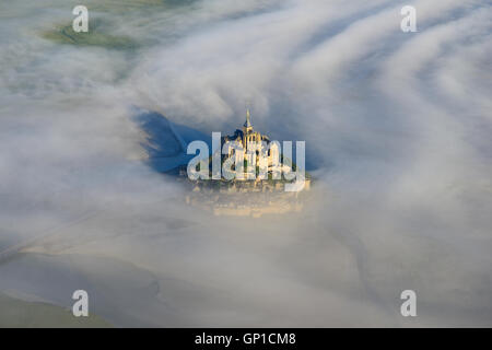 MONT SAINT-MICHEL SURROUNDED BY LOW MORNING FOG (aerial view). Manche, Normandy, France. - Stock Photo