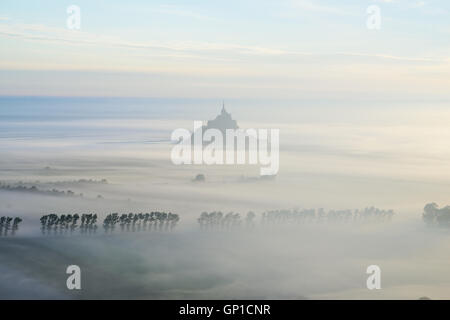 MONT SAINT-MICHEL SILHOUETTED AGAINST THE MORNING FOG (aerial view). Manche, Normandy, France. - Stock Photo