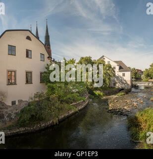Old mill at Kvarnfallet in the Fyris river with the Uppsala Cathedral (Domkyrkan) in the background, Uppsala, Sweden. - Stock Photo