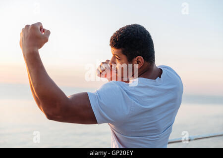 Muscular african american young man athlete standing and practicing shadow boxing outdoors - Stock Photo