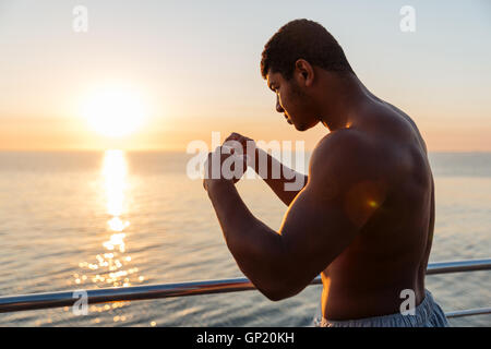 Silhouette of african american young man athlete doing boxing training in the morning - Stock Photo