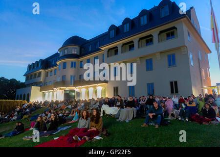 Spectators at an open-air movie night in front the Parliament building of the german-speaking Community in Eupen, - Stock Photo