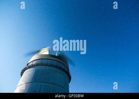 Rozhen astronomical observatory under the night sky stars. Blue sky with hundreds of stars of the Milky way. - Stock Photo